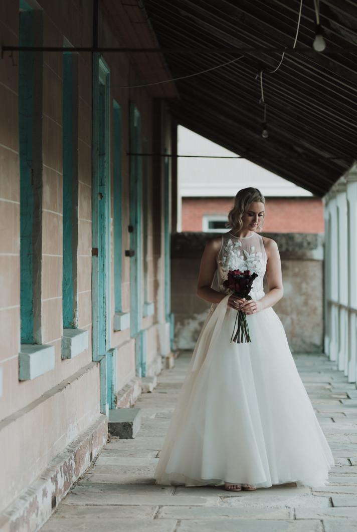 Bride walking along a veranda.