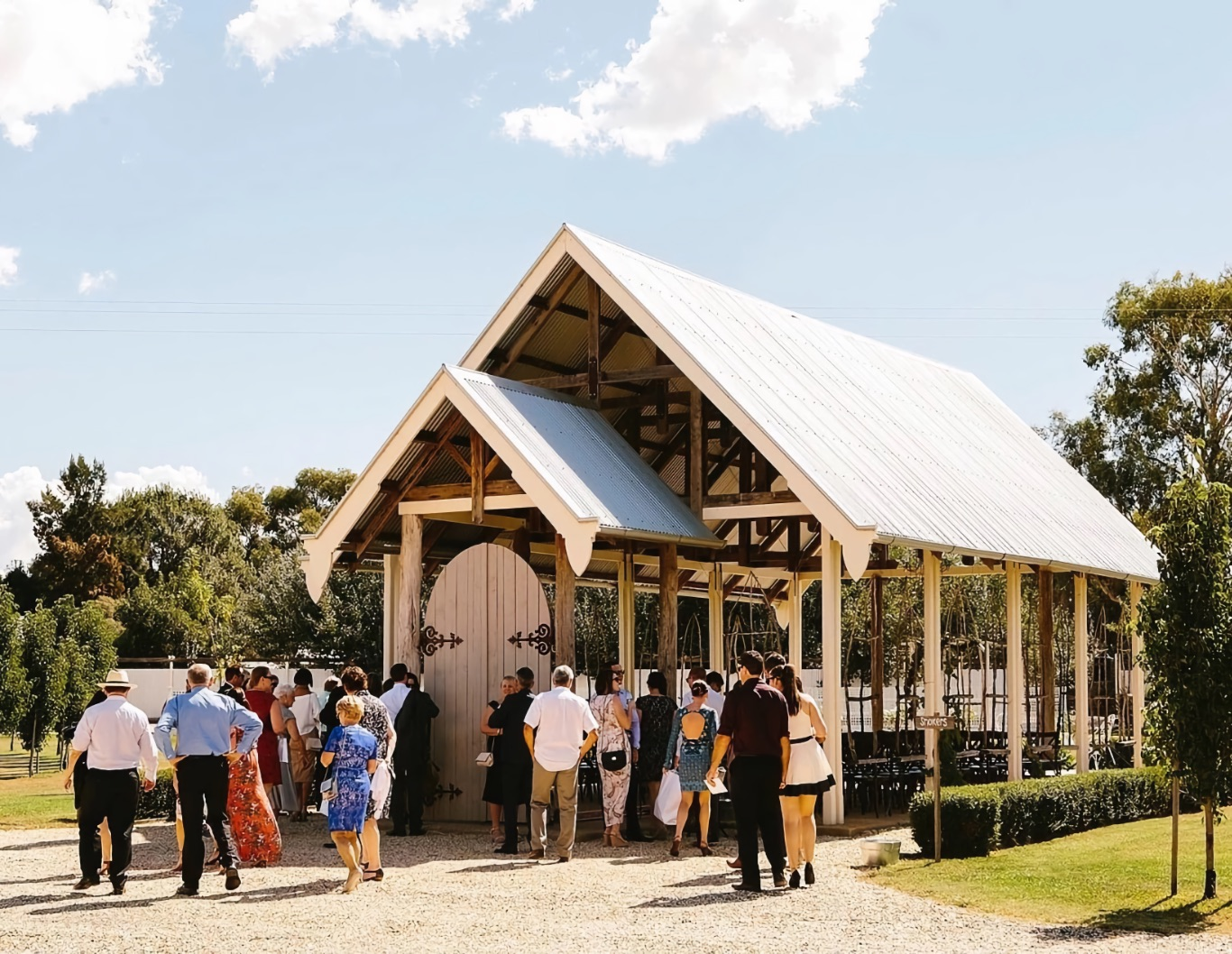 Wedding guests gather outside an open chapel.