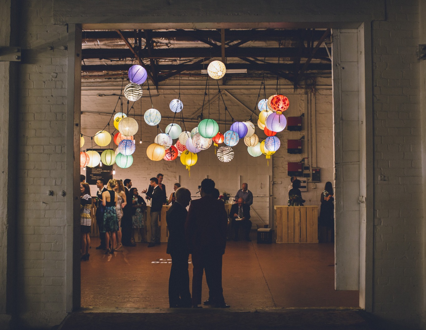Weddings guests under light installation inside a barn.