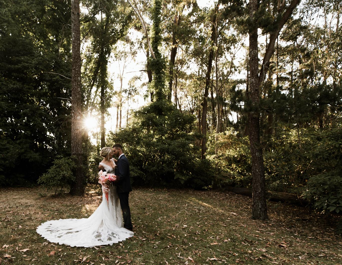Wedding couple embrace amongst sunlit bushland.
