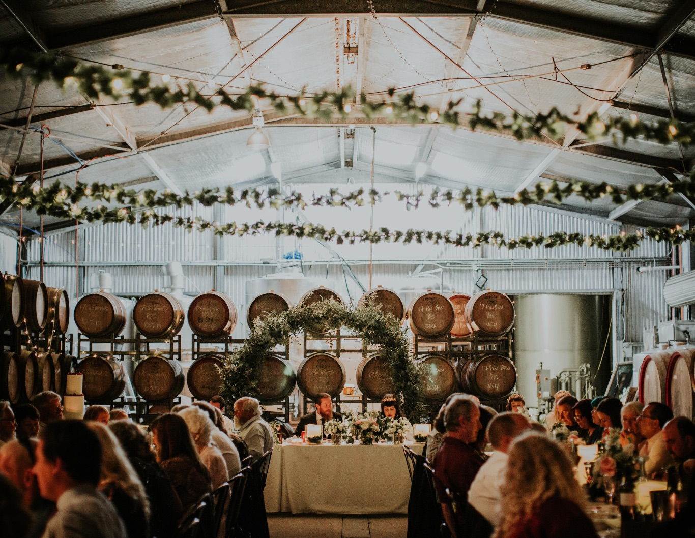 Couple sitting at wedding party table, with wine barrel racks behind them.